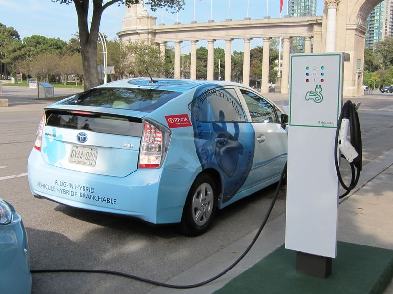 A charging station fills up a Prius PHEV