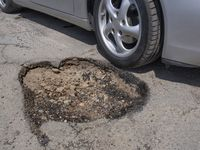 Potholes can cause serious damage to your vehicle - photo courtesy CARSTAR